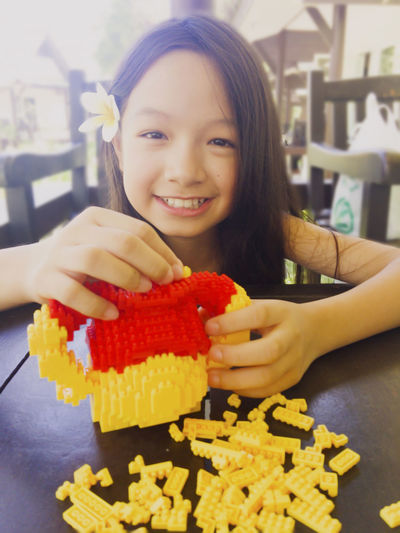 9 Years Old Blocks Happiness Play Time Asian Girl Black Hair Bricks Close-up Cute Education Enjoying Life Freshness Front View Game Girl Happiness Happy Girl  Indoors  Leisure Activity Lifestyles Looking At Camera Lovely Smart Girl Smiling Toy