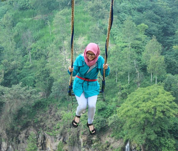 Full length of women climbing on rope in forest