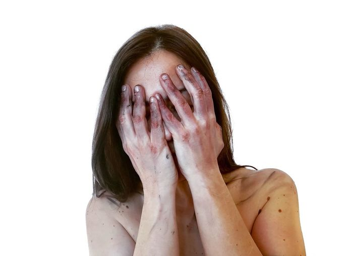 Portrait of a young woman covering face against white background