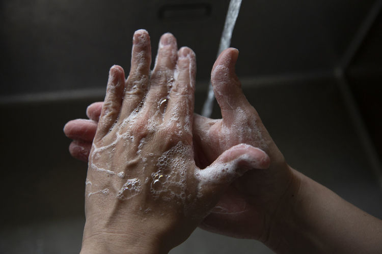 Close-up of person hand on wet floor