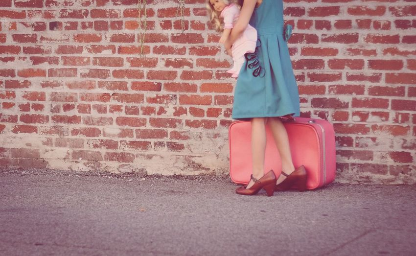 Low section of girl carrying doll and briefcase against brick wall