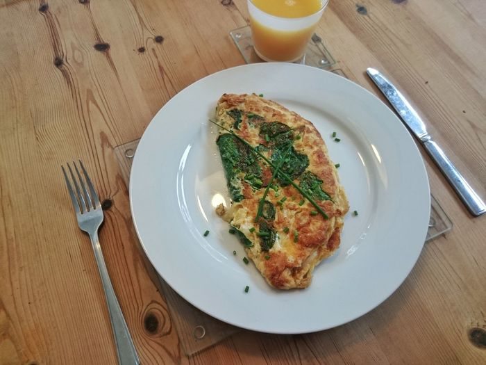 High Angle View Of Omelet By Drink On Wooden Table