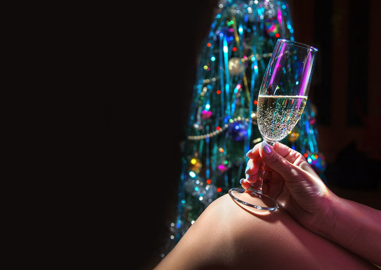 Midsection of woman holding champagne against black background