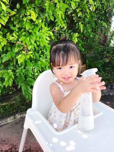 A Lovely Asian girl playing Architecture Front View Lifestyles Looking At Camera Portrait Fun Water Women water spray frothy for watering trees / Let your child get stained because it will be a learning experience. One Person Growth Childhood Real People Sitting Day Chair Tree Outdoors People