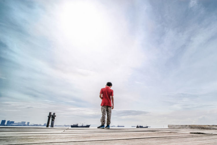 Rear View Of Boy Standing On Pier Against Sky