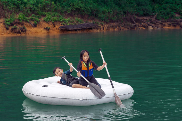 Cute girl and boy sitting on boat in lake