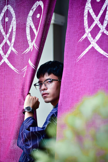 Portrait of young man standing by curtain