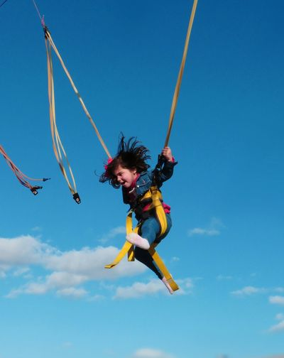 Low angle view of girl bungee jumping against blue sky