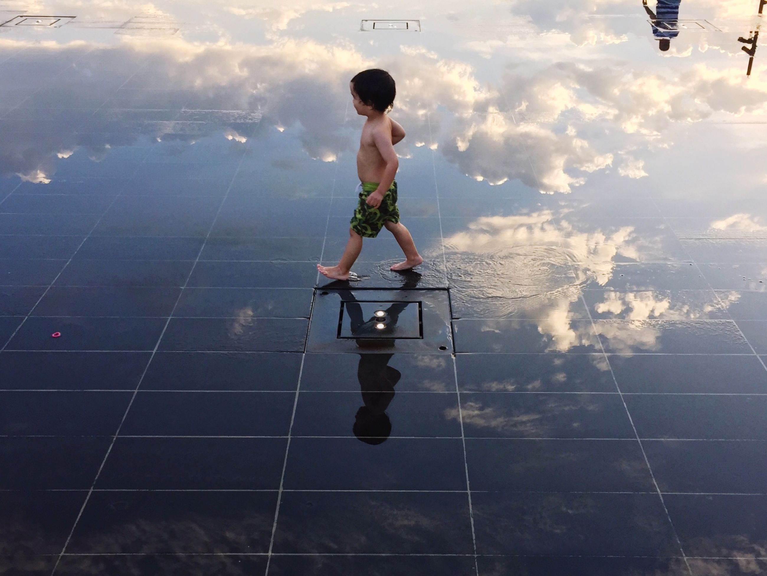 full length, lifestyles, leisure activity, sky, cloud - sky, water, childhood, boys, casual clothing, standing, fun, reflection, day, person, playing, high angle view, men, enjoyment