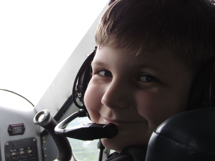 Portrait of boy with microphone sitting in airplane cockpit