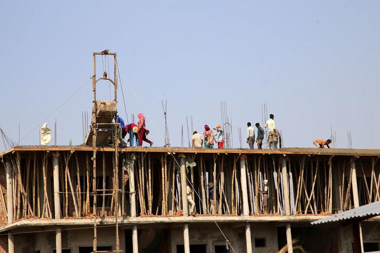 Low Angle View Of Workers At Construction Site Against Sky