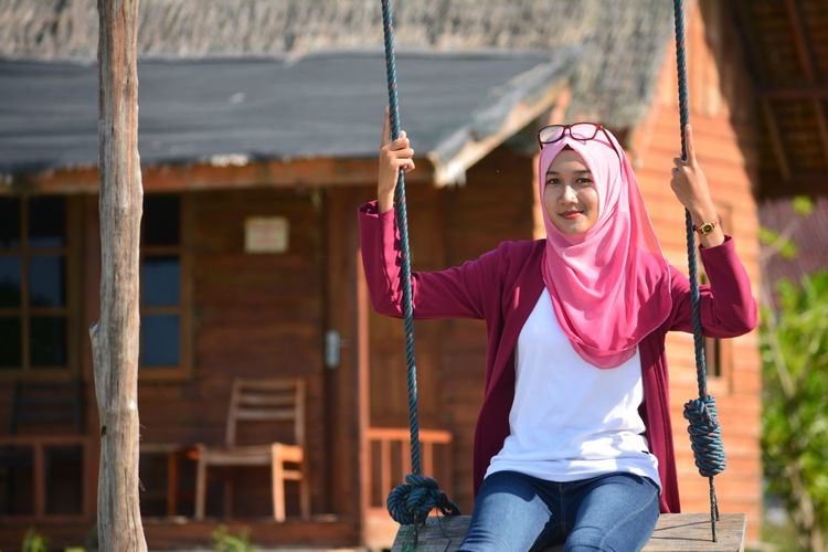 Portrait of young woman swinging on sunny day