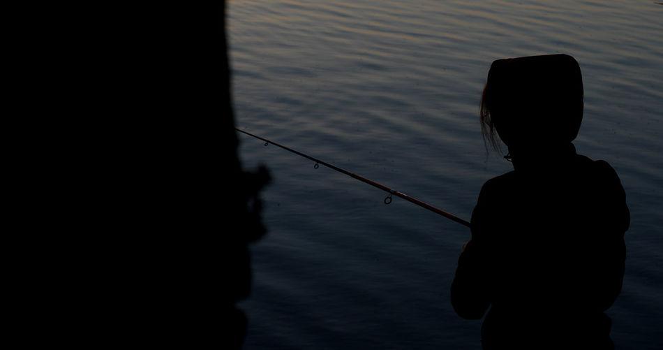 Rear view of silhouette man fishing in lake