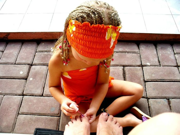 High Angle View Of Girl Applying Nail Polish On Mother Toenail