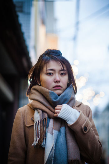 Portrait of young woman wearing warm clothing while standing in city