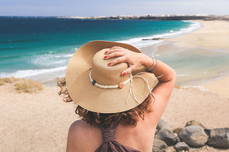 Rear view of woman with hat at beach