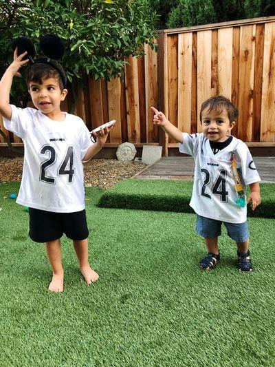 Full length of siblings standing in yard