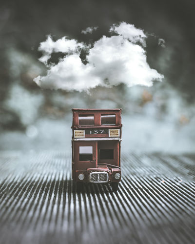 Digital composite image of toy car against clouds