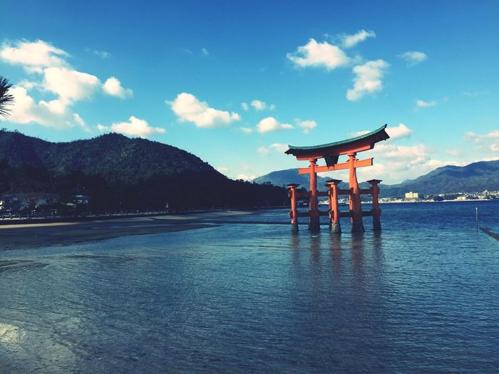 Itsukushima shrine in river against mountains and blue sky