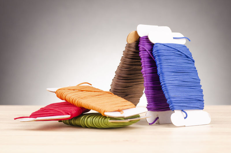 colorful stacking cotton yarn wool over beautiful reverberation gradient background. Indoors  Thread Multi Colored Still Life Table Spool Variation Art And Craft Choice Textile Sewing Item No People Close-up Wool Stack Studio Shot Focus On Foreground Copy Space Large Group Of Objects Gray Purple