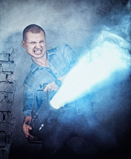 Digital Composite Image Of Angry Man Holding Lighting Equipment Against Brick Wall