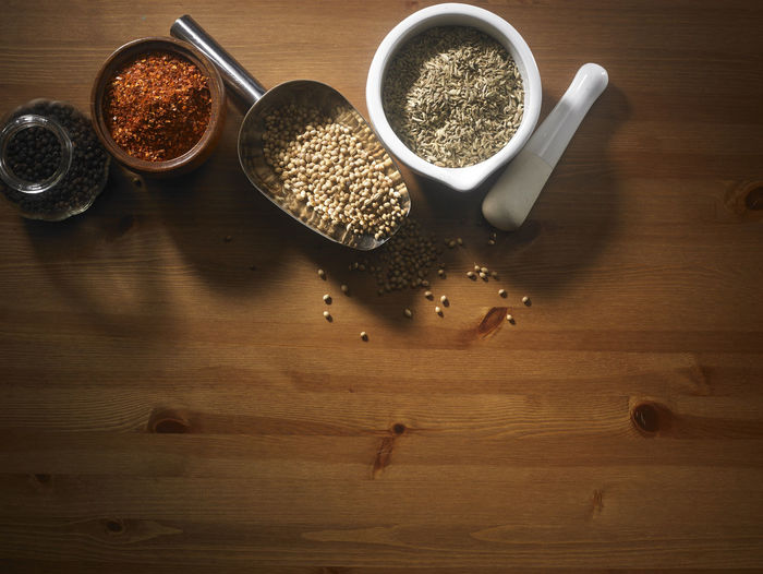assorted spices on the wooden table Chili Pepper Food And Drink Herb Seed Spoon Wooden Table Aroma Assortment Brown Chili  Condiment Coriander Cumin Directly Above Food Group Of Objects Ingredient Mortar And Pestle No People Paprika Pepper Scoop Shape Seasoning Spice Wood - Material