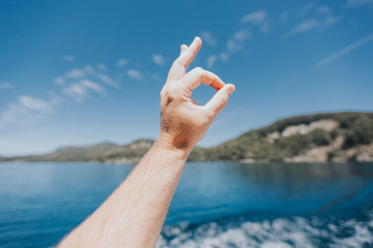 Close-up of hand against sea against blue sky
