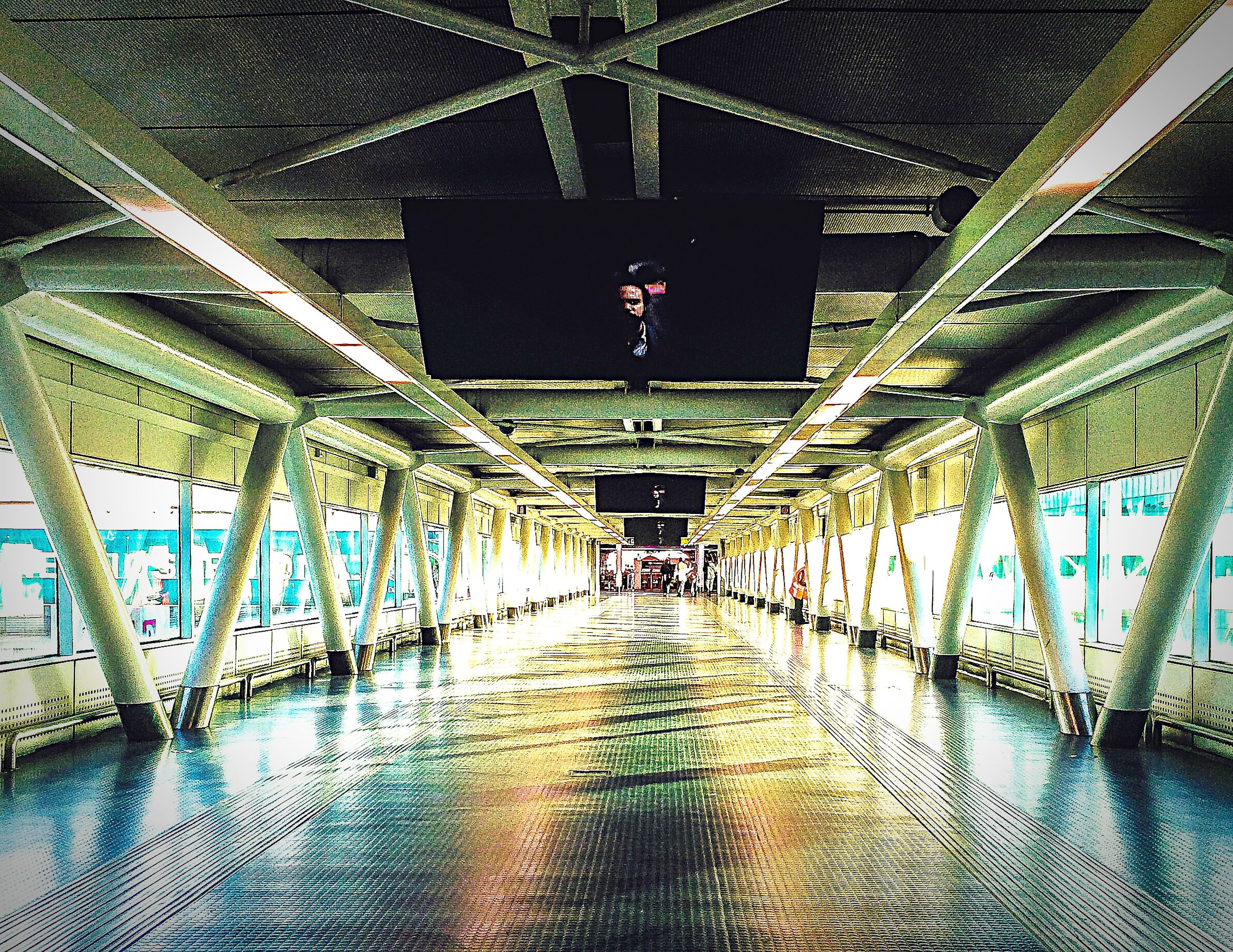 architecture, built structure, indoors, the way forward, diminishing perspective, ceiling, connection, metal, bridge - man made structure, vanishing point, engineering, walkway, illuminated, footbridge, pattern, lighting equipment, architectural column, empty, long, metallic