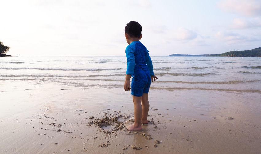 Full length of boy standing at beach against sky