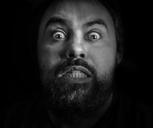 Close-up portrait of angry man with beard against black background