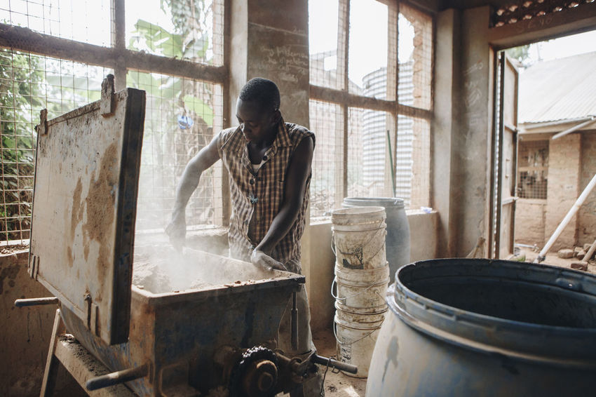 Africa African Business Ceramic Clay Dirty Dust Entrepreneurship Factory Filter Indoors  Man Manual Worker Manufacturing Mixing One Person Pottery Social Business Water Filter Worker Working Working Workshop Young Adult