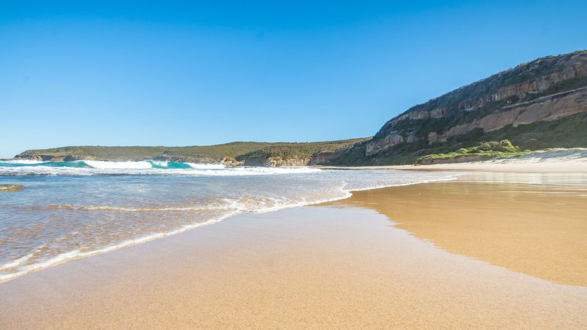An untouched beach in Australia on a perfect sunny day Water Beach Land Sea Sky Beauty In Nature Scenics - Nature Clear Sky Sand Tranquil Scene Nature Tranquility Blue Outdoors Wave Sport Motion Mountain Aquatic Sport Surfing