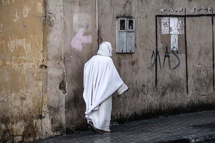 Rear view of moroccan woman in traditional clothing walking along historic wall