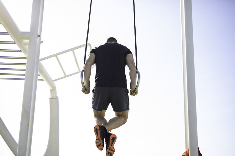 Low angle view of man exercising on gymnastic rings against sky