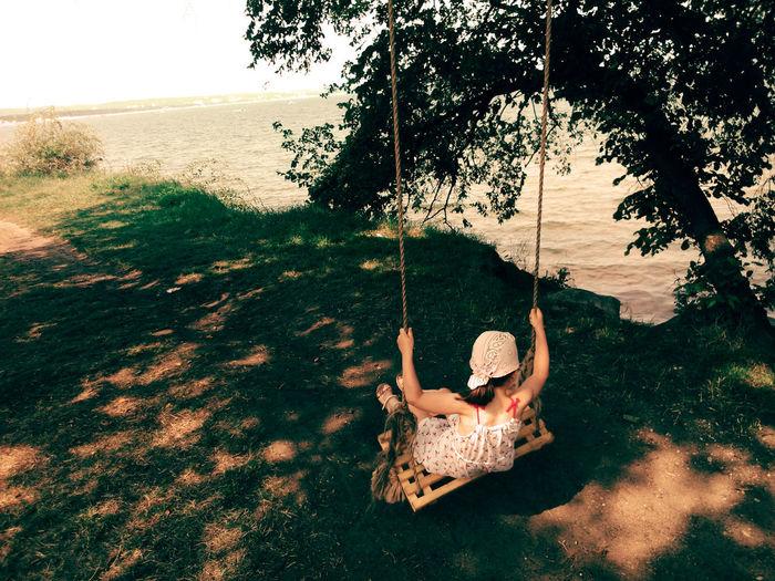 Child sitting on swing