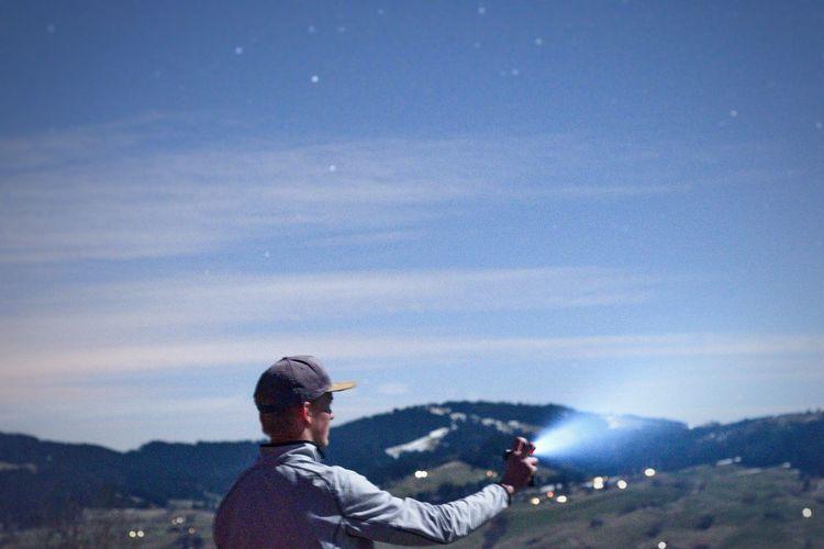 Man holding flashlight against sky