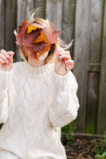 A young woman in casual clothes have a fun with autumn leaves outdoor.