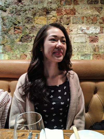 Happy young woman sitting at restaurant