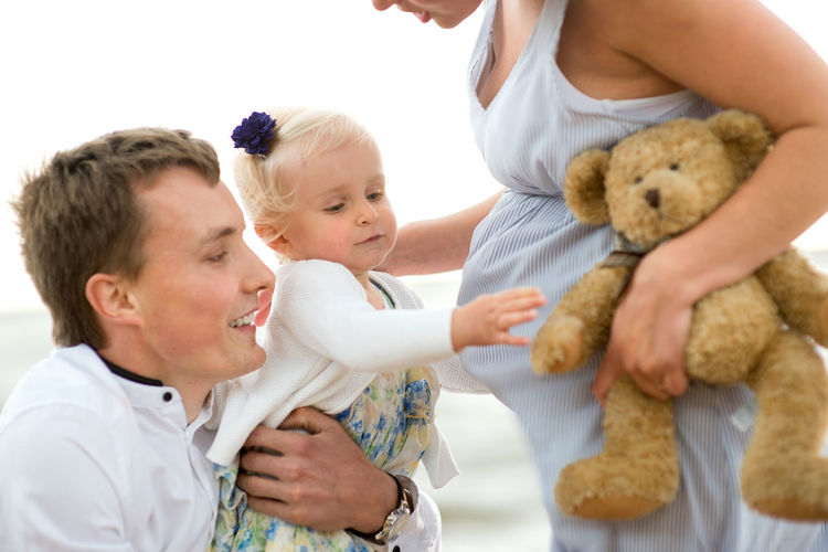Baby girl with father and pregnant mother at beach
