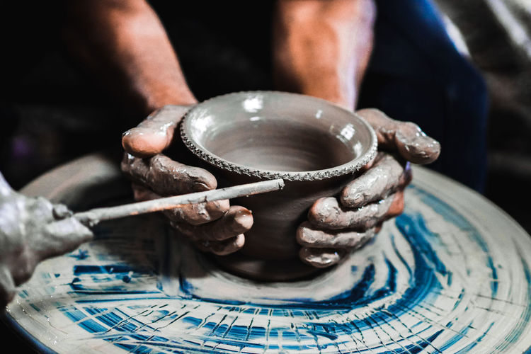 Cropped hands making pot on pottery wheel