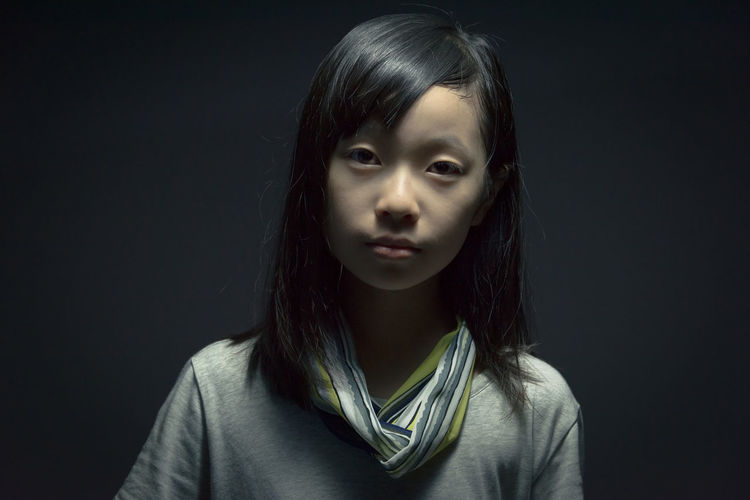 Asian girl portrait at studio light Asian  Calm Cool Hopeless MOVIE Thinking Black Background Childhood Chinese Close-up Day Dramatic Front View Girl Headshot Indoors  Looking At Camera One Person Portrait Real People Serious Stare Story Studio Shot Young Adult