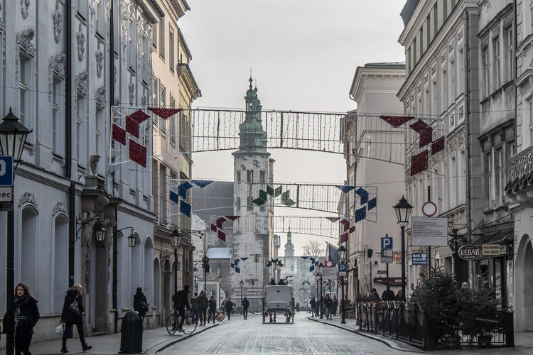 The medieval city street full of magic City Poland Winter Architecture Building Building Exterior Built Structure City Cold Cracow Day Direction Incidental People Krakow Lifestyles Medieval Men Old Outdoors Real People Sky Street The Way Forward Transportation Women