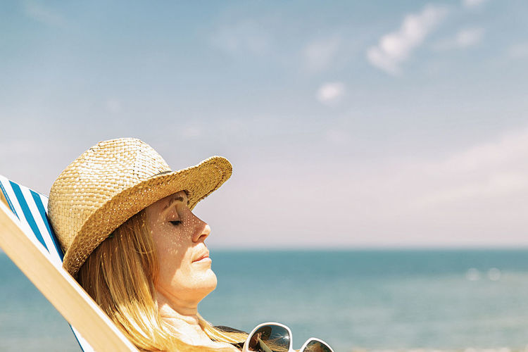 Portrait of young woman with hat on beach against sky