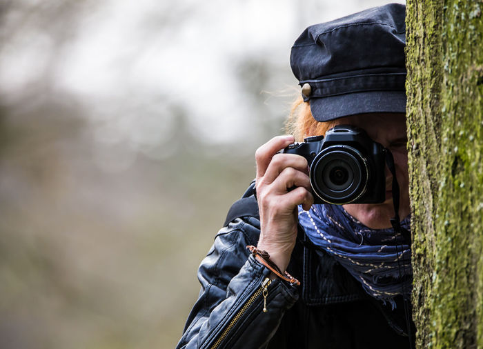 Woman photographing through camera by tree