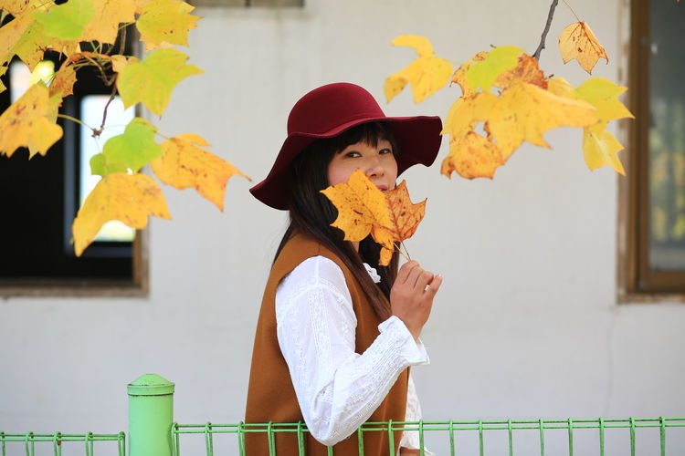Portrait of woman with hat standing against wall during autumn