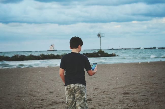 Internet Addiction Wireless Technology Technology Smart Phone Holding Connection Person Photography Themes Outdoors Communication Sea Beach Water Horizon Over Water Rear View Shore Sand Full Length Casual Clothing Standing Sky Lifestyles Cloud Lighthouse Scenics Creative Space The Great Outdoors - 2018 EyeEm Awards