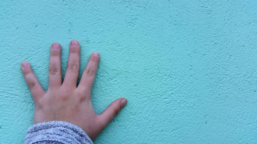 Cropped image of hand against green wall