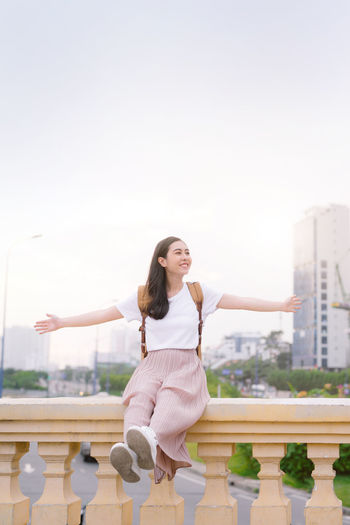 Beautiful asian girl is having a rest outdoors Asian  Vietnamese Adult Architecture Arms Raised Building Exterior Built Structure City Hairstyle Happiness Human Arm Human Limb Leisure Activity Lifestyles Limb Nature One Person Outdoors Sky Standing Three Quarter Length Women Young Adult Young Women