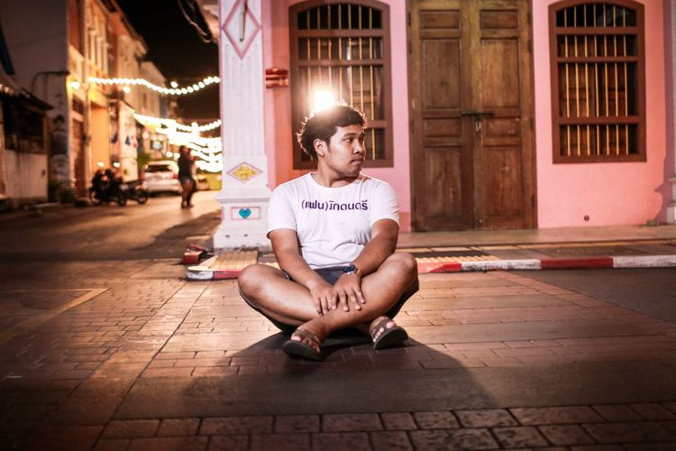 Man sitting on footpath in city at night
