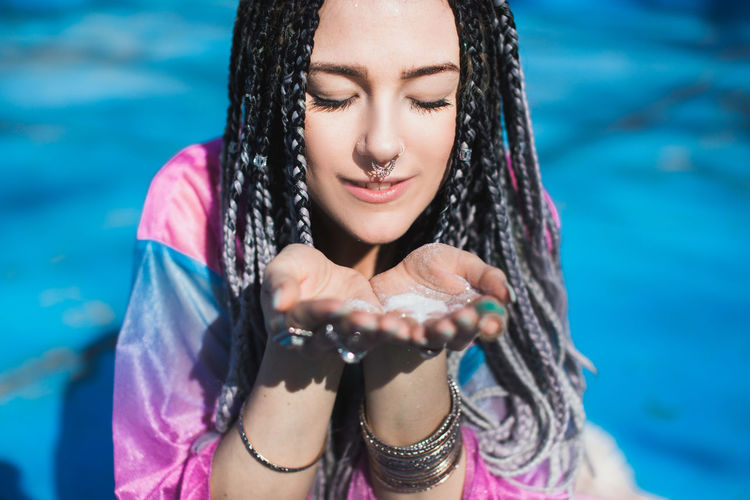 Beautiful woman with braided hair blowing glitter Braids Cool Glitter Hair Hands Pink Shining Sparkle Beautiful Woman Beauty Blowing Festival Glow Hairstyle Outfit Portrait Sunshine Turquoise Young Adult
